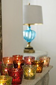 Coloured tea light holders with burning candles on a shelf and a lamp with a blue glass base on the window sill