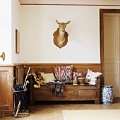 An anteroom in a country house - a wooden bench with wood panelling and an animal head on the wall