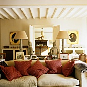 An upholstered sofa with red cushions and oriental figures in a rustic country house