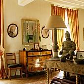 An oriental wooden figure and Biedermeier furniture in a living room