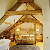 An attic room with a rustic wood beam ceiling and a four poster bed made of bamboo wood