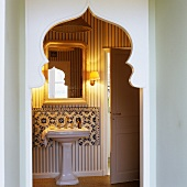 A view through an Oriental pointed archway onto a wash basin with an ornamental foot and a mirror above