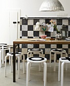 A playful dining room - black and white patterned stools and a wall and a wooden table