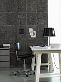 Black and white - a white desk with a black desk chair against an dark wood panelled wall