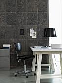 Schwarzweiss - weisser Schreibtisch mit schwarzem Bürostuhl vor dunkler holzvertäfelter Wand