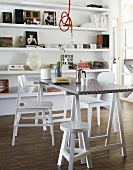 A coffee break on a trestle table with white chairs in front of a shelf
