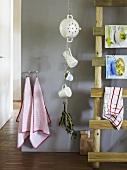 An arrangement in a kitchen - crockery hanging against a grey wall