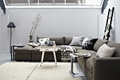 Relaxation in the conservatory - a grey corner sofa and a white flokati rug
