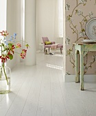 A boudoir with white floor boards and gloriosa flowers in a vase