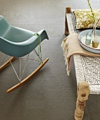 A rocking bucket chair next to a coffee table on a grey tiled floor