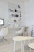A white corner of a room with a group of stools and a designer chair in front of a workbench below a wall shelf
