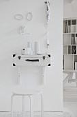 Künstlerisch gestaltete Wand mit selbstgebautem Konsolentisch und weißem Hocker