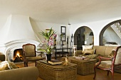 A sofa and wicker tables in Mediterranean living room with arched doorways