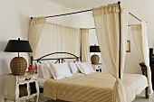 A metal four poster bed with a natural-coloured curtain and a vintage bedside table