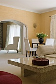 A shiny stone coffee table and a dining area with a view through a rounded archway of an armchair
