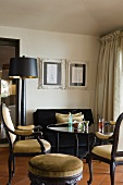 Upholstered antique chairs and a glass table in the corner of the room