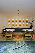 A massage room with a pool - wooden loungers in front of a wall niche and burning candles