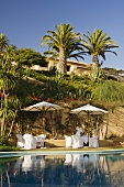 Haus am Hang mit Palmen - Pool mit Bar unter Sonnenschirm
