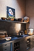 Corner of a Mediterranean kitchen - bowls on a shelf and a work surface with dark grey fitted cupboards