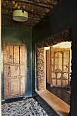 An anteroom with rustic doors and a view into the next door room of a Mediterranean country house