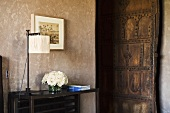 A table lamp on a side table and view of an open rustic door