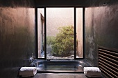 A concrete bathroom - a sun bathtub filled with water in front of a floor-to-ceiling window with a view of a courtyard