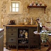 Storage jars on an old kitchen drawer unit in front of a rustic, natural stone wall