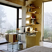 A desk with a panoramic view - an armchair and a glass table with a shelf in the corner of a room with floor-to-ceiling windows