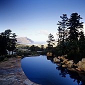A view over a bright blue pool of the impressive South African landscape