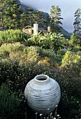 A white amphora in a field with a view of a South African country house set in the wilderness