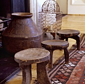 Three rustic wooden stools in front of an amphora