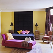 A colourful bedroom - a pink chaise longue with a black bed in the background with a ceiling-high headboard on the yellow wall