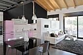 Schwarzer Tisch im Designer-Wohnraum mit offener Küche im Fifties-Stil unter Holzbalkendecke