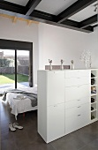 An open-plan bedroom with a low cupboard acting as a room divider in front of a bed and view of the garden