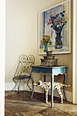 A wall table and an ornamental metal chair in front of a painting