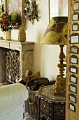 An antique table lamp on an intarsia side table with a view of a fireplace