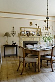 A living room in a country house with a laid table with antique chairs and rustic floor boards
