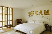 A bedroom with closed wooden blinds - a bed with a white cover and the word 'Dream' on the wall