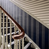 A wooden stairway with a striped pattern on the wall