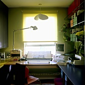 Green shimmering light in a study with a desk lamp on the desk and blinds at the window