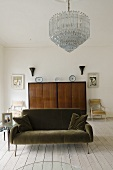 A brown sofa with a chandelier with a Biedermeier cupboard in the background in a room with floor boards