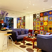 A purple sofa in front of a mirrored wall and a large abstract picture of bright coloured circles