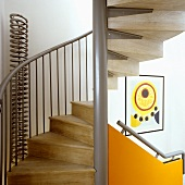A spiral staircase with a metal frame and wooden stairs and a handrail on an orange-colored panel