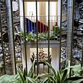 Blick vom Innenhof auf raumhohe Fenster mit Einsicht und künstlerisch gestalteter Fassade