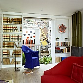 A living room with a blue chair and a built-in shelf with a view of an artistically designed wall in the courtyard