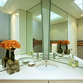 A mirrored cabinet in a bathroom - a corner wash basin with a white stone surface