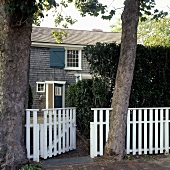 A detached house with a white garden fence