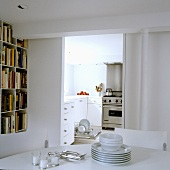 Crockery being tidied - a view through to a kitchen with an open dishwasher