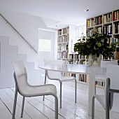 A round table with chairs in front of a bookshelf wall with a stairway in the background