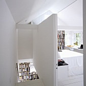 A partitioned attic room with a white stairway and a view into a bedroom